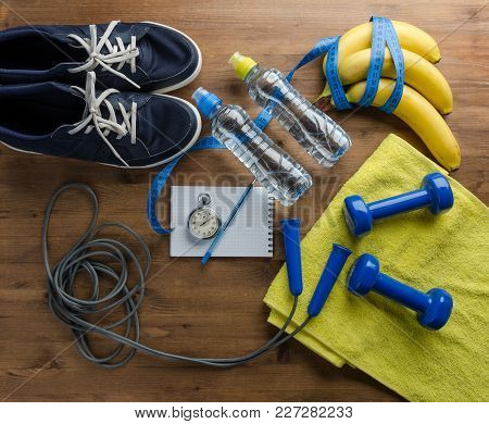 Fitness Concept With Sneakers Dumbbells Stopwatch Measure Tape Towel Bottle Of Water And Bananas On