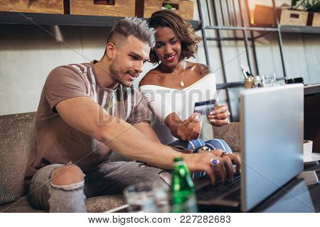 Mixed Race Couple Buying Online With Credit Card And Laptop In A Coffee Shop