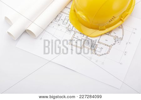Architectural blueprints, safety helmet, pencil on a white background. Architect workplace. Engineering tools. Top view.