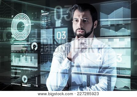 How Interesting. Smart Concentrated Attentive Programmer Standing In Front Of A Futuristic Screen An