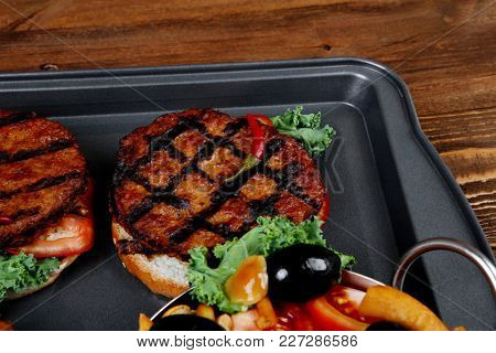 fresh red meat beef hamburger served on black tray with vegetables olives hot chili pepper tomatoes mushrooms over wooden table