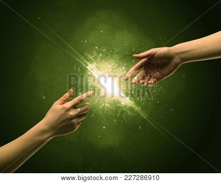 Two naked male hands about to touch, lighting the spark with modest explosion in front of green background concept
