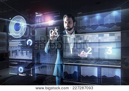 Counting. Calm Concentrated Elegant Programmer Looking Attentive While Standing In His Dark Modern O