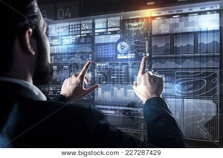 Finding Connection. Clever Calm Experienced Programmer Touching Two Icons On The Transparent Screen