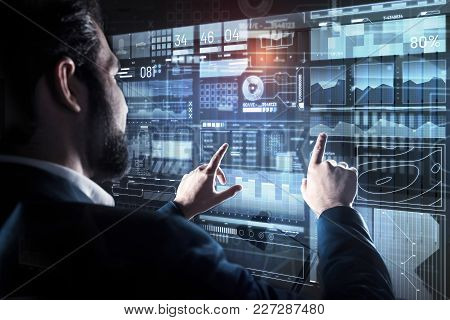 Comparison. Calm Experienced Bearded Programmer Touching The Transparent Screen With Two Fingers Whi