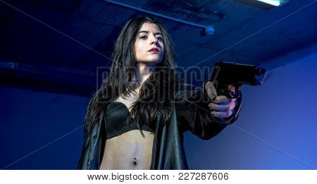 Spy, armed and dangerous girl in a parking lot, wearing a black leather jacket and a bulletproof vest