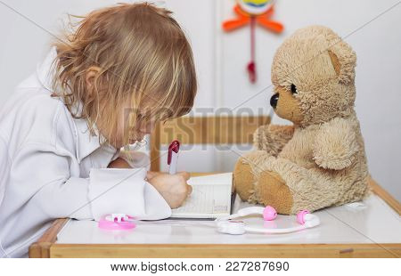 Little Girl Playing A Doctor With Her Teddy Bear