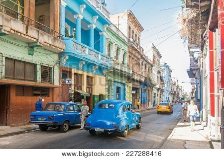 Havana, Cuba - January 16, 2017: Street Scene With Colorful Buildings And Old American Car In Downto