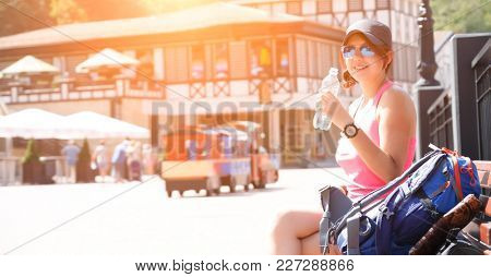 Photo of woman in sunglasses with bottle of water