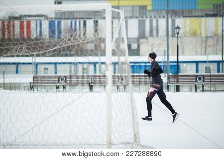 Photo of running athlete in black clothes near gate in stadium