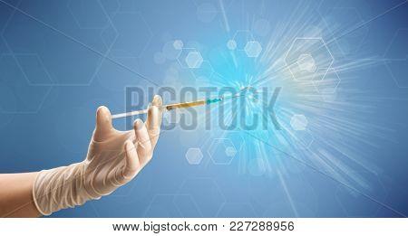 Female doctor hand holding syringe with shiny background