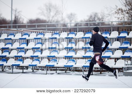 Photo of running athlete in black clothes at stadium