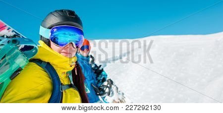 Panoramic photo of cheerful couple with snowboard on background of snowy hills