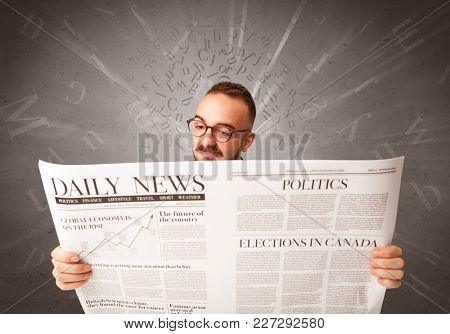 Young smart businessman reading daily newspaper with alphabet letters above his head