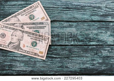 American Dollars On A Green Wooden Background.