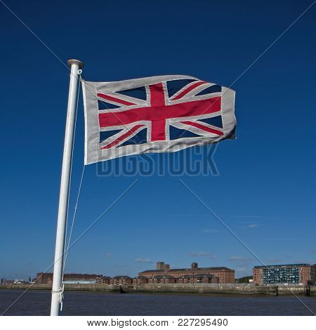 British Flag Waving On The Wind. Clear Blue Sky In The Background.