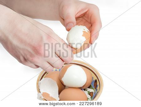 Boiled Brown Chicken Egg In Human Hands During Cleaning From Eggshell Over Of Bowl With Other Eggs A