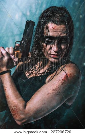 Fearless agent woman holding a hand gun in action under the rain