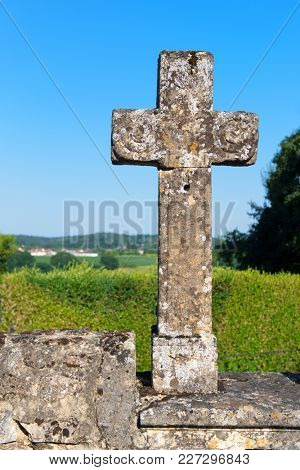 Old stone cross with moss against landscape