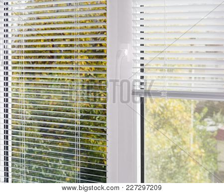 Inside View Of Part Of The Modern Plastic Window With White Venetian Blinds, Partly Raised On One Ha