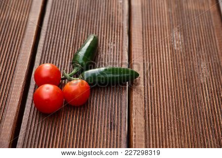 A Conceptual Composition Of Red Cherry Tomatoes And Hot Green Chili Peppers On Dark Brown Wooden Boa