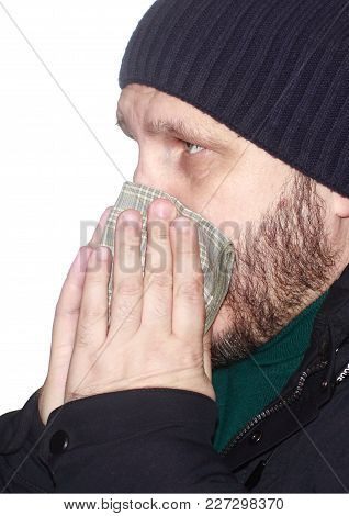 A Sick Bearded Man In A Warm Down Jacket And Knitted Hat, Blowing His Nose In A Handkerchief