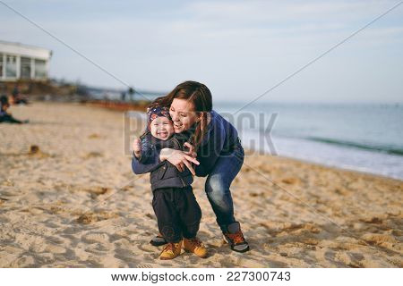 Young Woman Playing At Sea Sand Beach Background With Little Cute Child Baby Boy, Good Mood. Mother,