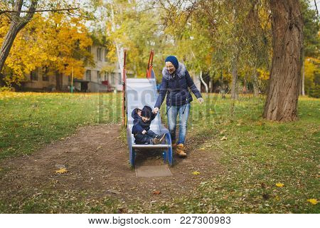 Young Woman Walk In Green Yellow Fall Autumn Park With Little Cute Child Baby Boy On Nature. Mother,