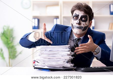 Businessmsn with scary face mask working in office