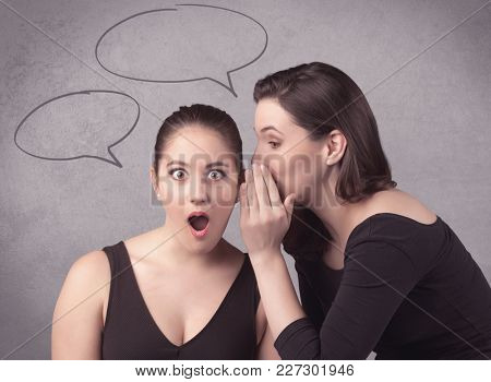 Two girls chatting and sharing their secrets concept with drawn chat bubbles on the background urban wall.