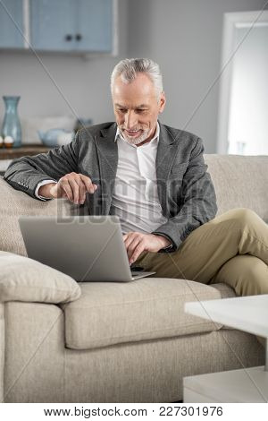 Online Job. Delighted Elderly Male Person Expressing Positivity While Checking News And Sitting On H