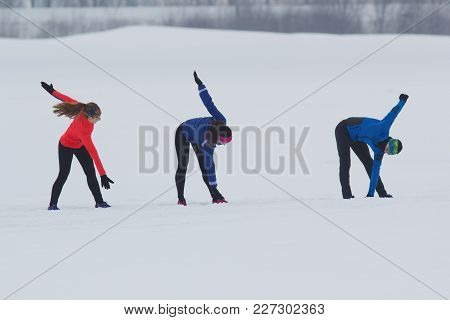 Group Of Athletes Doing The Exercise In Winter Forest, Sport And Leisure Concept