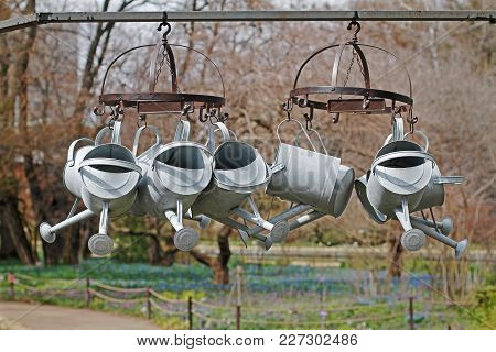 Metal Steel Watering Cans Hanging On The Dryer Outdoors