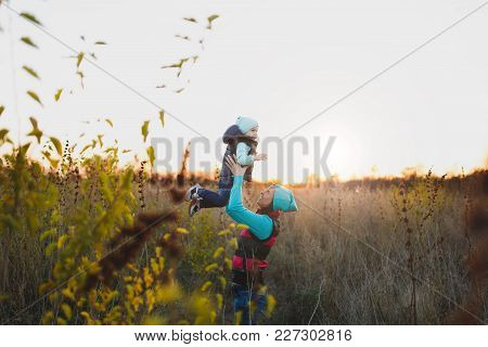 Woman In Turquoise Hat Standing At Dry High Grass Background High Toss Up Little Cute Child Baby Boy