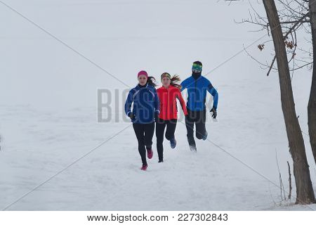 Group Of Athletes Jogging In Winter Forest, Sport And Leisure Concept