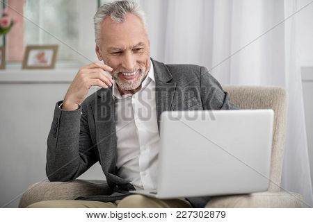 High Spirits. Cheerful Man Feeling Happiness While Looking At Screen Of His Laptop And Raising Right