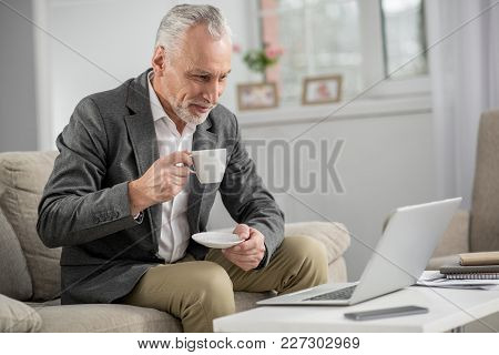 Keep Your Attention. Attractive Businessman Holding Cup In Right Hand And Keeping Smile On His Face