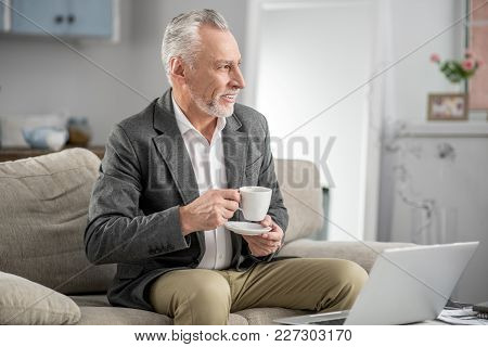 Deep In Thoughts. Positive Delighted Bearded Male Person Keeping Smile On His Face And Turning Head