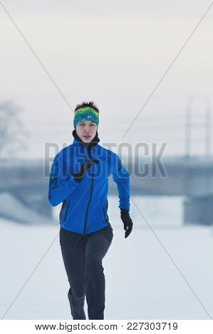 Young Male Athlete Running In Winter Through The Snow, Sport And Leisure Concept