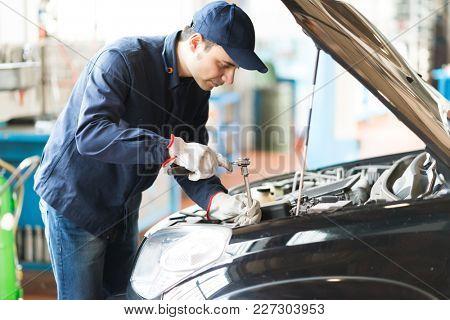 Mechanic repairing a car in his garage