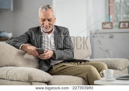 Good Mood. Attractive Bearded Male Person Keeping Smile On His Face And Looking At His Telephone Whi