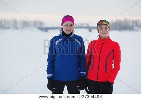 Portrait Of A Two Young Female Athletes Is Posing In Winter Ice Field, Sport And Leisure Concept