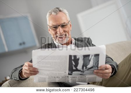 Enjoy Your Life. Handsome Male Person Being At Home, Keeping Smile On His Face While Reading Article