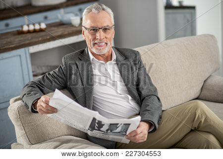 Joyful Mood. Positive Delighted Man Crossing Legs While Sitting On His Sofa And Smiling On Camera
