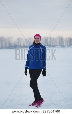 Portrait Of A Smiling Young Female Sportswoman In Winter Ice Field, Sport And Leisure Concept