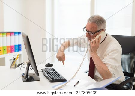 Annoyed businessman having a discussion while talking on the phone