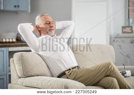 Time To Dream. Positive Delighted Bearded Man Crossing Legs While Sitting On The Sofa, Stretching Ar