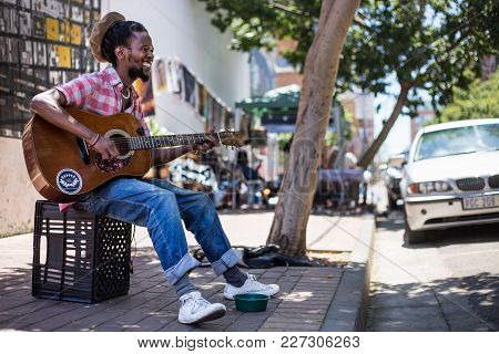 Johannesburg, Gauteng, South Africa, 20018/01/10. A Busker Singing And Playing Guitar On The Streets