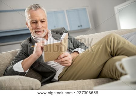 Positive Worker. Cheerful Male Person Keeping Smile On His Face And Holding Notebook While Sitting O