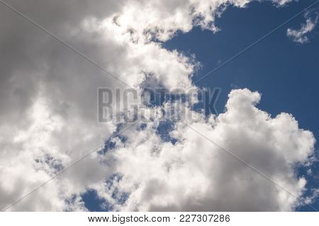 Dramatic Fluffy White Billowy Clouds Brightly Back Lit Creating Shadows And Strong Highlights, With